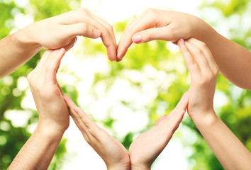 Hands in shape of heart, on blurred nature background