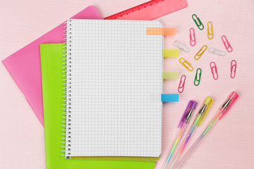 Office set with notebooks, colored pens and clips on pink background