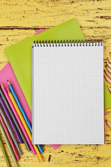 Office set with notebooks and pencils on yellow wooden background