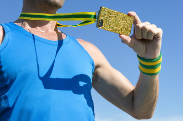 Athlete taking a selfie with his gold medal mobile phone against bright blue sky