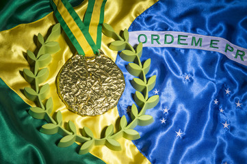 Large gold medal surrounded by laurel wreath resting on shiny Brazil flag background with studio lighting