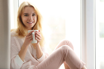 Blonde beautiful  girl sitting and smiling by the window with cup of tea or coffee in her hands