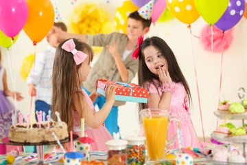 Happy little girl presenting a gift to her friend at birthday party