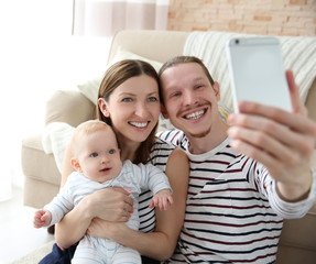 Happy couple taking a selfie with baby, close up