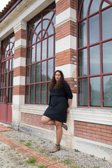 Fashion outdoor portrait of sensual brunette woman with black dress