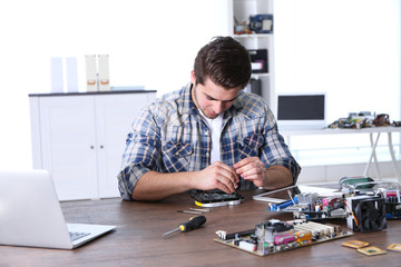 Man fixing electronic circuits in service center