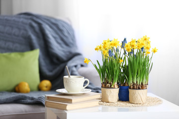 Photo sur Plexiglas Narcisse Blooming narcissus flowers with books and cup of tea on table, indoors