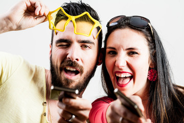 thrilled couple taking mobile photographs and selfies