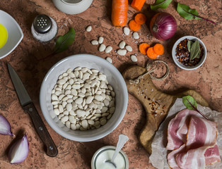 White beans, bacon, carrots, red onion, spices and herbs - ingredients for making bean mash with bacon. On a stone background. Top view