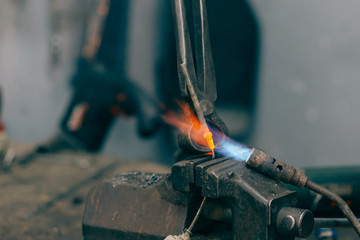 Metalworker working with torch and repair metal. Selective focus and small depth of field.