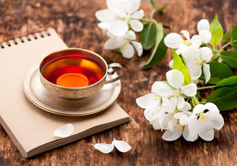 Tea cup, notebook and white spring flowers on a wooden table