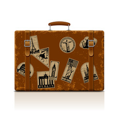 Vintage brown threadbare suitcase with retro travel labels