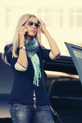 Fashion business woman in sunglasses calling on the phone next to car