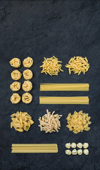 Different types of Italian uncooked pasta on black slate stone background with copy space above, top view