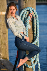 A shot of a beautiful Caucasian fashion woman on the pier at boat marina.