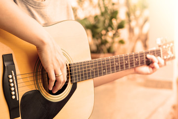 Woman's hands playing acoustic guitar with vintage style