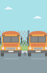 Yellow buses on the background of mesh fence.