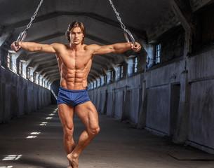 Bodybuilder male model posing with gimnastic rings.