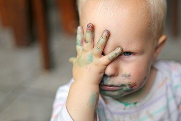 One Year old Baby Girl Covering her messy painted face with her little hand