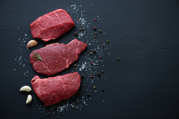 Deurstickers Vlees Fresh uncooked marbled beef schnitzels on a black wooden surface