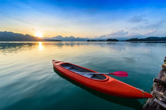 Canoe floating on the calm water under amazing sunrise