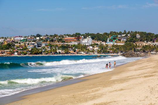 Puerto Escondido, Mexico - January 25th 2014 - Few people enjoying a sunny day in a desert beach in Puerto Escondido, Mexico