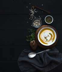 Pumpkin soup with cream, seeds and spices in rustic metal bowl over black background. Top view.