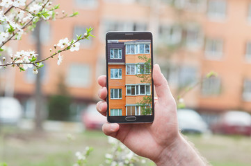 Hand with smartphone taken pictures of multi-storey building