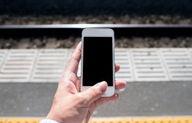 駅のホームでスマートフォンを操作する男性