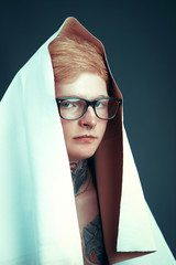 A young blond man in glasses with a pierced nose and a tattoo throwing on his head a white cloth.Guy model with a good figure posing on dark background in Studio
