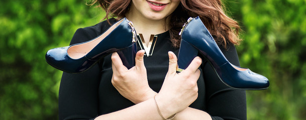 girl holds shoes in hands