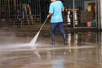 worker cleaning floor with air high pressure machine background