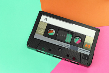 Audio Compact Cassette C60 tape with a blank label on a colored background