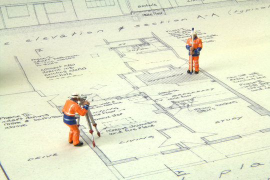 Two miniature figures in high-vis uniform with a theodolite survey a house blueprint