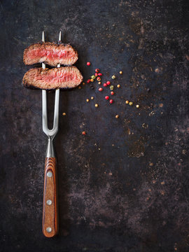 Steak on meat fork with peppers
