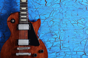 Brown electric guitar on blue wooden background