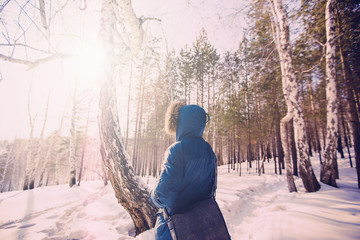 a man with a hood and a bag in the winter forest