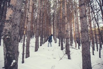 a man in a hood looking at forest plantations in the winter