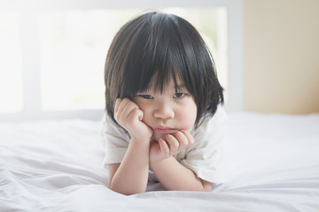 unhappy asian baby lying on white bed