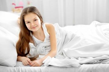 Little girl awake in bed
