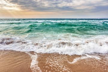 sea waves crashing on sandy beach