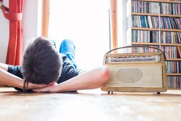 Junger Mann hört Musik mit altem Radio