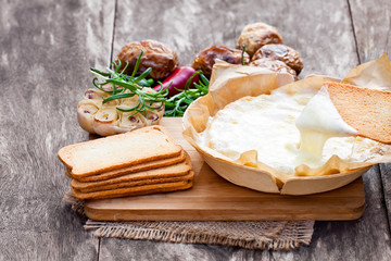 Delicious  baked camembert with roasted potato and toast