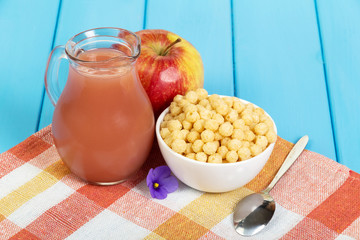 Apple juice in a jug and corn balls into bowl on  wooden background okreshennogo blue.