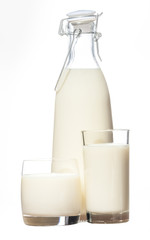 A bottle of rustic milk and two glasses  of milk