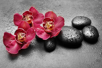 Spa stones and red orchid on grey background