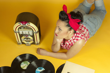 Portrait beautiful pin up listening to music on an old jukebox r