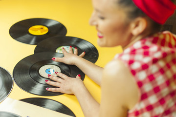 Rear view portrait pin up girl with old vinil records. Selective