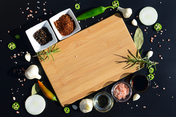 Food background. Empty cutting board and pepper, bay leaf, rosemary, onions, Himalayan salt, olive oil, soy sauce on a black background. The template for displaying products