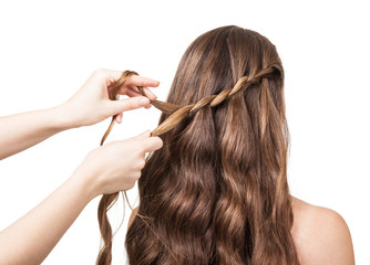 Hands hairdresser braided lock of the girl with long hair isolated on white .